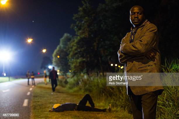 Men gather on a road leading to the Eurotunnel terminal in Coquelles on August 2 2015 in Calais France Hundreds of migrants are continuing to attempt...