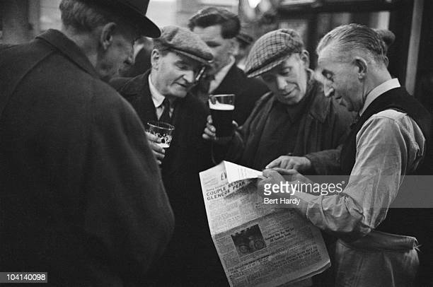 Men gather to look at a newspaper in a bar in the Gorbals area of Glasgow, January 1948. Original publication: Picture Post - 4499 - The Forgotten...