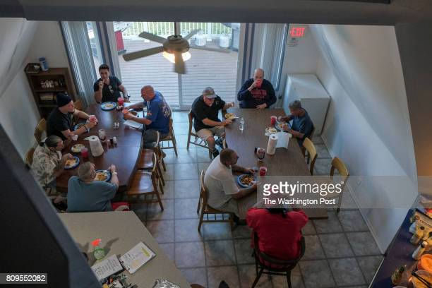 Men gather together for their nightly dinner at Champ House an allvolunteer recovery house that services men suffering from addiction on Tuesday June...