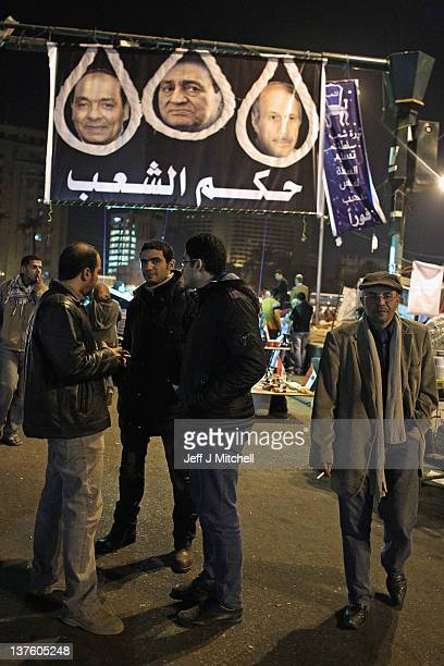 Men gather under a banner showing nooses around the heads of Field Marshall Hussein Tantawi Former President Hosni Mubarak and former police chief...