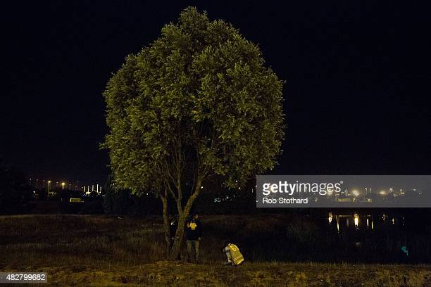 Men gather under a tree near the Eurotunnel terminal in Coquelles on August 3 2015 in Calais France Hundreds of migrants are continuing to attempt to...