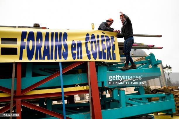 Men gesture on a truck next to a sign reading 'fun fair workers angry' outside the Grand Palais in Paris on December 21 2017 during a protest against...