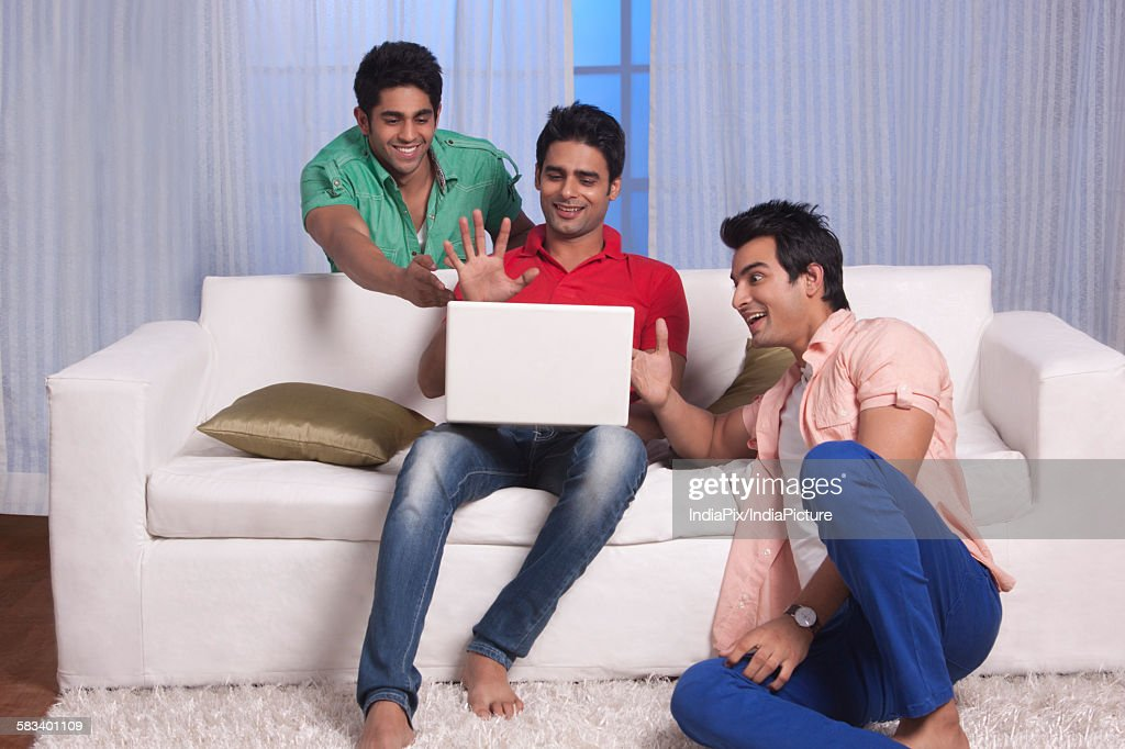 Men gesturing at their friends laptop : Stock Photo