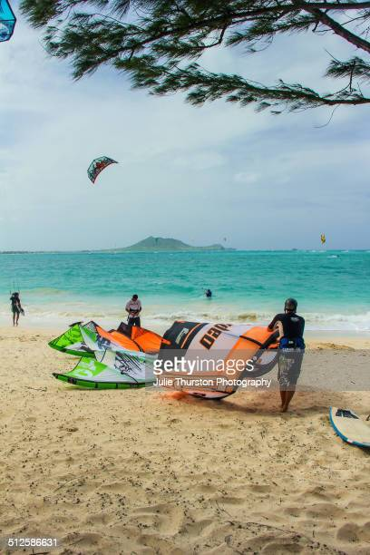 Men Get Their Colorful Kiteboard Sails Ready on the Beach to Head into the Water To Enjoy Some Recreation Kiteboarding in the Pacific Ocean With The...