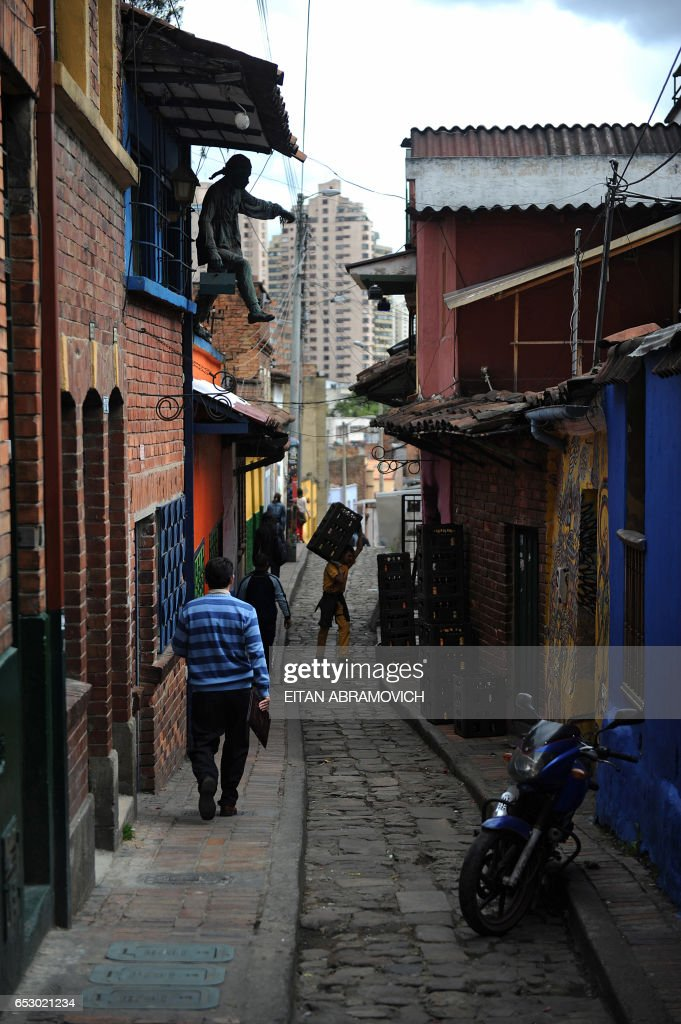 Men go about their business in a narrow street in the historic neighborhood of La Candelaria in Bogota on September 17, 2009. La Candelaria is Bogota's oldest neighbourhood and the city's historical center, known for its colonial houses with wooden balconies and clay shingle roofs. AFP PHOTO/Eitan Abramovich -------------- MORE
