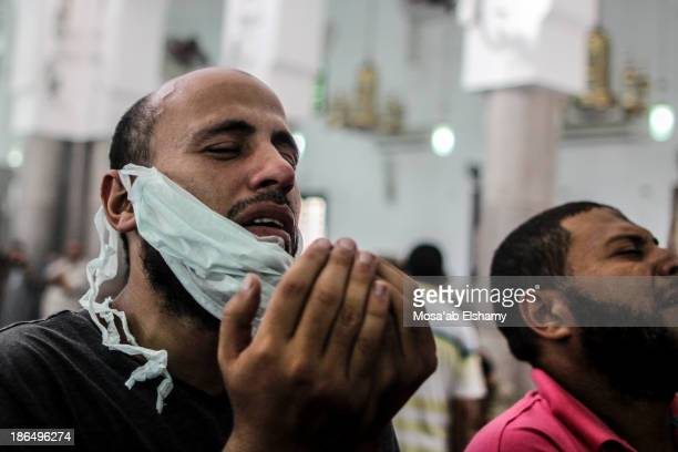 Men grieve while praying at Iman mosque which was turned into a makeshift morgue following the violent dispersal of Rabaa Adaweya square and the...