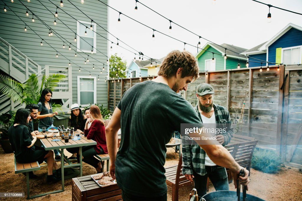 Men grilling food for friends during backyard barbecue : Stock Photo