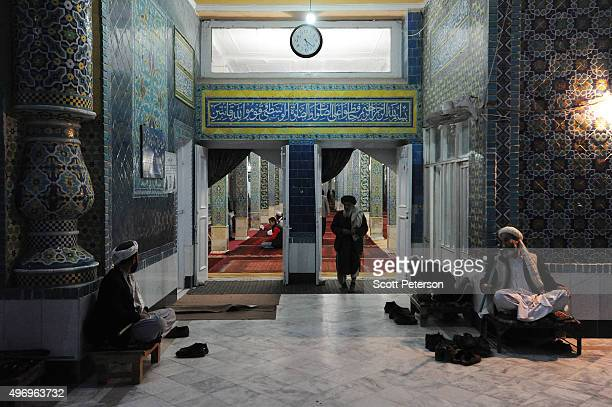 Men guard shoes for Afghans attending prayers in a hall beside the ancient Blue Mosque as Afghans go about daily life despite security fears of a...