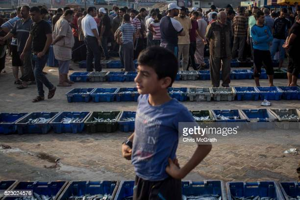 Men haggle over the price of crates of fish brought in by Gaza's fishermen at the port on July 22 2017 in Gaza City Gaza Gaza's fishermen suffer...