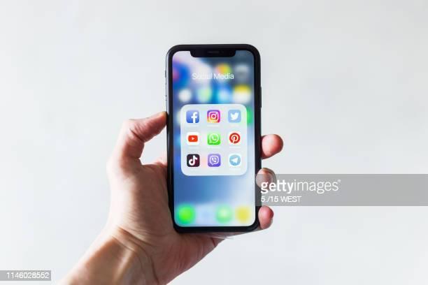 mão dos homens que prendem o smartphone com ícones de meios sociais - filtro de pós produção automática - fotografias e filmes do acervo