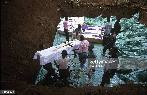 Men handle coffins into a mass grave in December of 1996 in Rwanda Africa In 1994 Rwanda saw one of the worlds worst act genocide to date At least...
