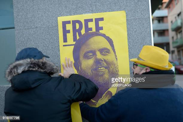 Men hang a poster depecting Catalonia's jailed former vice president Oriol Junqueras on a wall during a demonstration marking 100 days of...