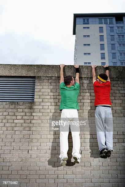Men Hanging from Wall