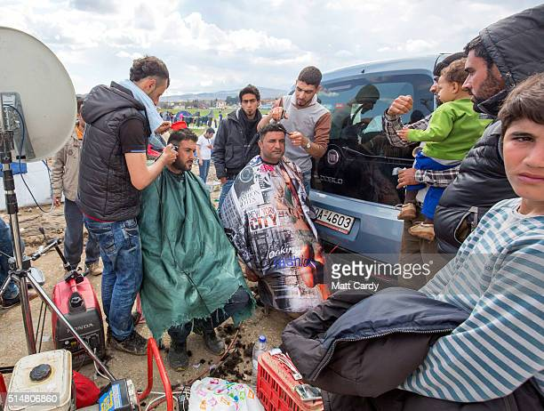 Men have their hair cut by two barbers who have set up inbetween media vehicles at the Idomeni refugee camp on the Greek Macedonia border on March 11...