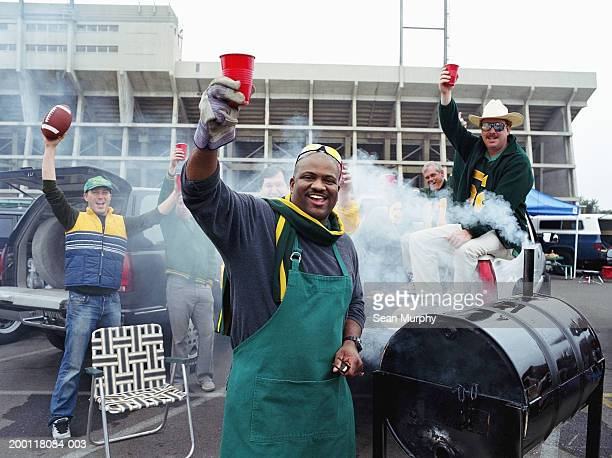 Men having barbeque at tailgate party  in stadium parking lot
