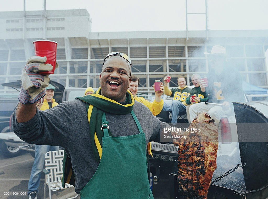 Men having barbeque at tailgate party  in stadium parking lot : Stock Photo