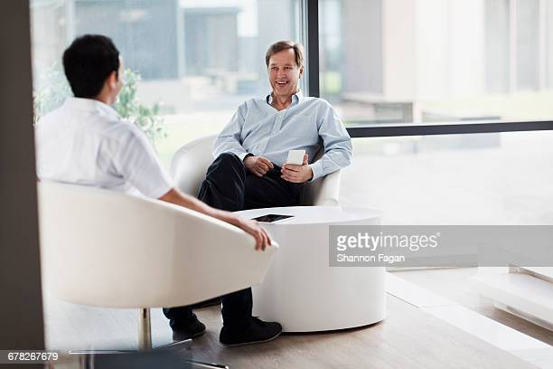 Men having conversation in meeting room lounge