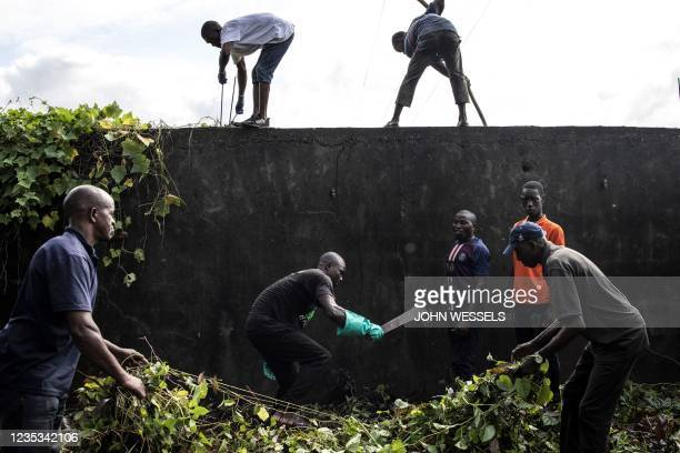 Men help to clean the famous Bambeto Cemetery in Conakry on September 18 as the Bambeto cemetery is where most opposition supporters who lost their...