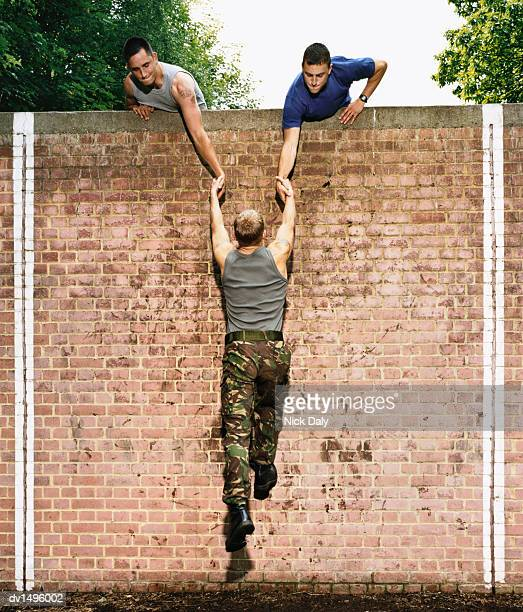 men helping a man to climb a brick wall on an assault course - obstacle course stock photos and pictures