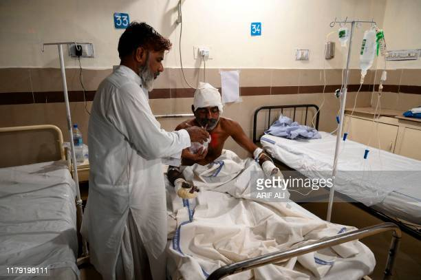 Men helps an injured victim to drink as he treated at a hospital in Bahawalpur on October 31 after a passenger train caught on fire in Rahim Yar Khan...