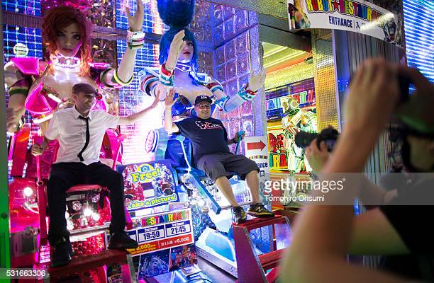Men highfive as they sit in robot chairs outside the Robot Restaurant in the Shinjuku area at night on May 13 2016 in Tokyo Japan