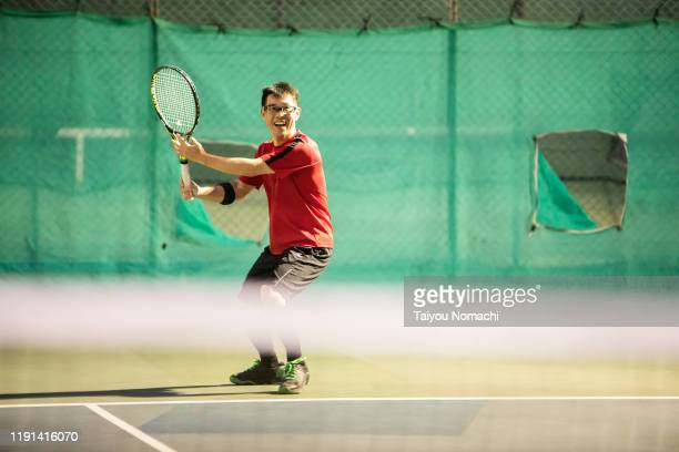 men hitting serve - racket sport stock pictures, royalty-free photos & images
