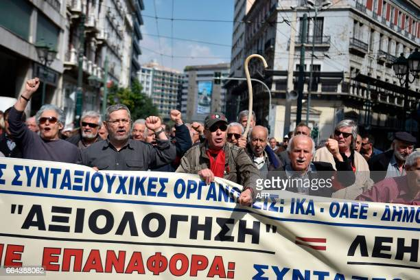 Men hold a banner gesture and chant slogans as they gather to march with hundreds of pensioners in central Athens on April 4 2017 to protest against...