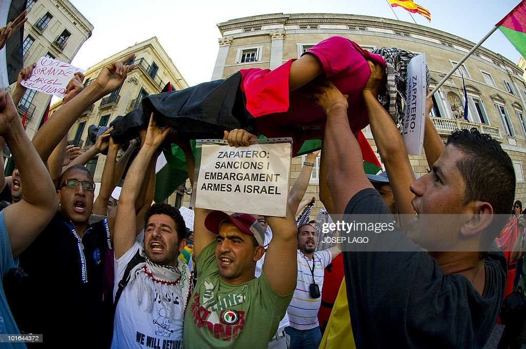 Men hold a person posing as a dead body during a demonstration in Barcelona on June 05, 2010 following a deadly Israeli military raid on the Gaza-bound flotilla of aid ships. Spain, which holds the rotating EU presidency, condemned the Israeli army's raid on aid ships bound for Gaza and summoned Israel's ambassador.
