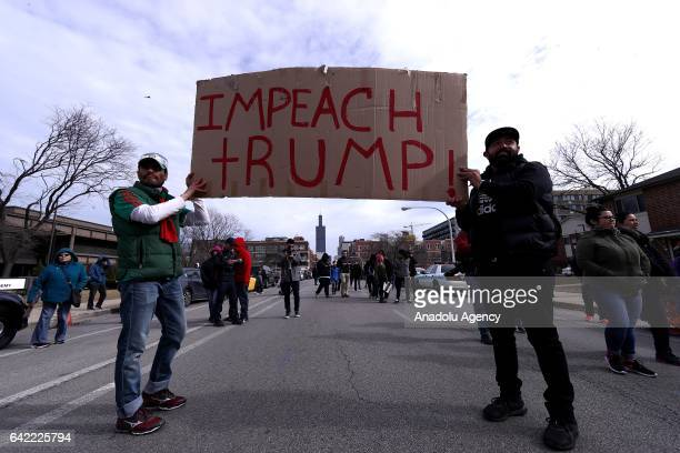 """Men hold a placard reading """"Impeach Trump"""" during a rally against US President Donald Trump's order and his recent policies regarding cracking down..."""