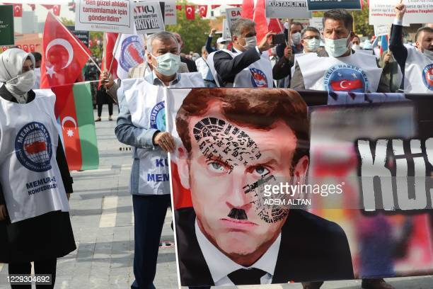 Men hold a sign bearing a picture of French President Emmanuel Macron with a shoe print on it as Turkish protesters shout slogans during a...