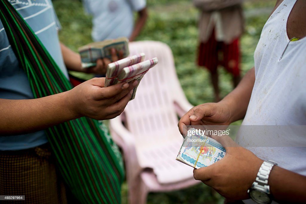 Men hold bundles of Myanmar Kyat banknotes at Thirimingala Market in Yangon, Myanmar, on Monday, Oct. 12, 2015.Myanmar's government signed a cease-fire agreement with half of the nation's armed ethnic groups, a partial victory for President Thein Sein less than a month before an historic national election. Photographer: Brent Lewin/Bloomberg via Getty Images