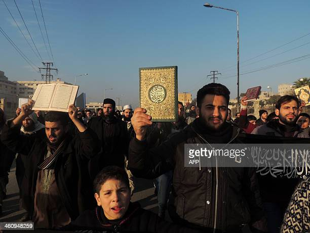 Men hold Koran holy book as they demonstrate outside the offices of the AlQaedalinked Islamic State of Iraq and the Levant demanding that they stop...