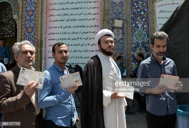 Men hold their identity cards as they wait to cast their ballots during Iran's 12th presidential election at Shah Abdol Azim mosque in Tehran Iran on...
