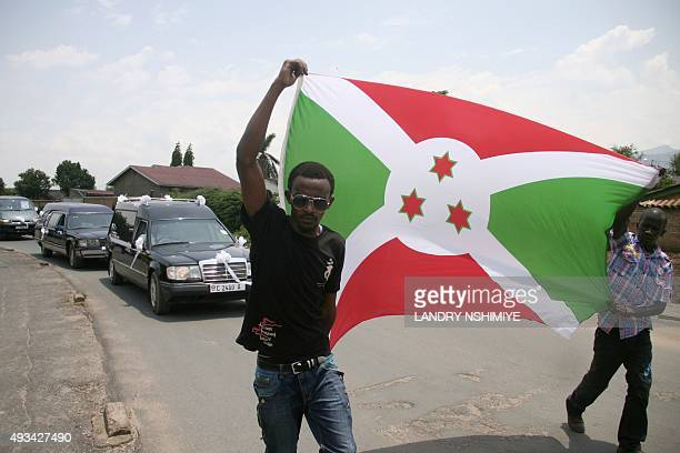 Men hold up a Burundian flag as they walk in front of the hearses during the funeral of a Burundian journalist and his family in Bujumbura on October...