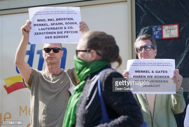 Men hold up signs deriding German politicians health experts and Bill Gates as a woman wearing a protective face mask walks past during a protest...