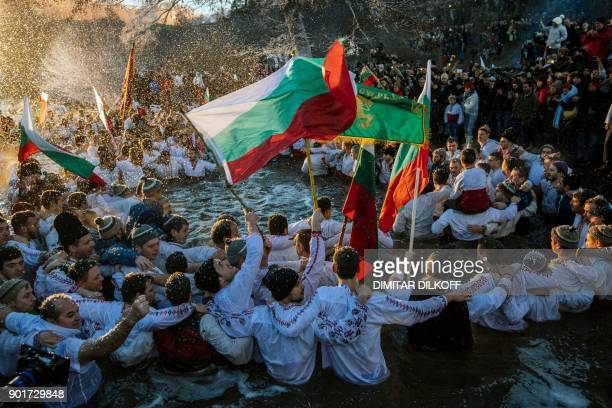 Men hold up the Bulgarian flag as they dance in the cold winter waters of the Tundzha River in the town of Kalofer Bulgaria on January 6 as part of...