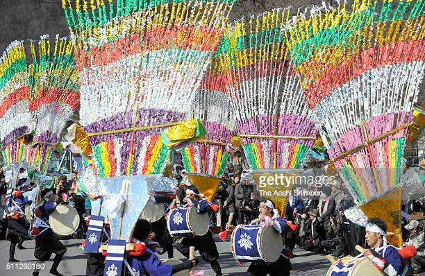 Men holding bamboo ornaments called 'Shinai' on their back perform taiko Japanese drums during the Tanigumi Odori dance on February 18 2016 in...