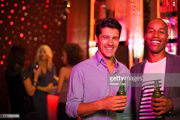 Hommes tenant des bouteilles de bière dans un night-club