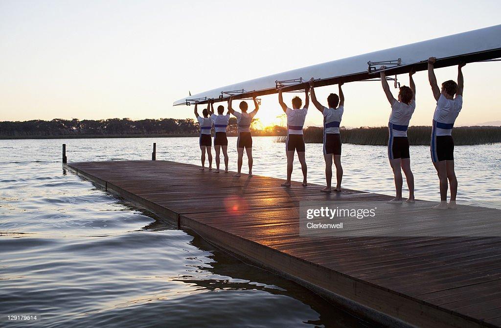 Men holding canoe over heads : Stock Photo