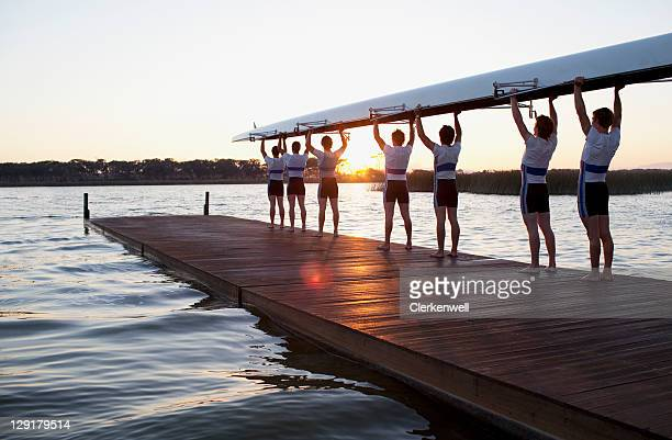 men holding canoe over heads - teamwerk stockfoto's en -beelden