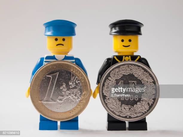 LEGO men holding Euro and Swiss Franc coins