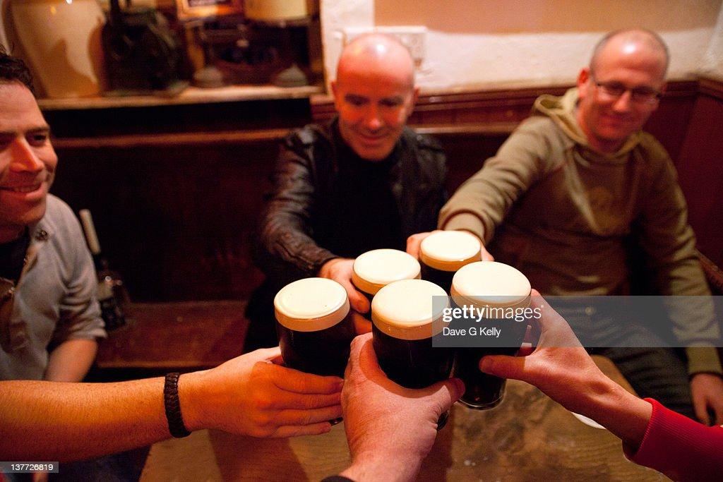 Men holding glasses of stout : Stock Photo