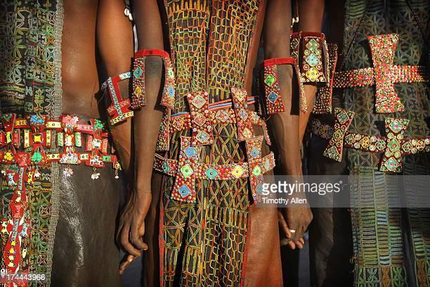 Men holding hands wearing tribal designs