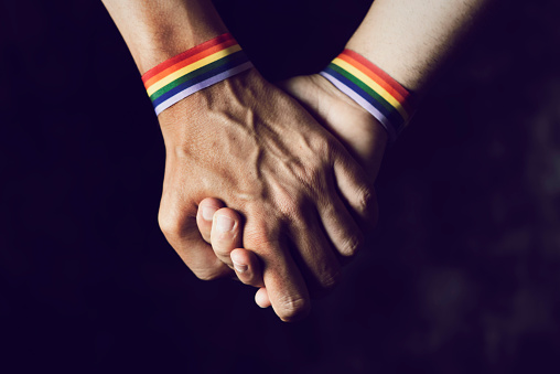 men holding hands with rainbow-patterned wristband 980764484
