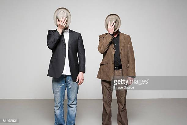 Men holding hats over their faces