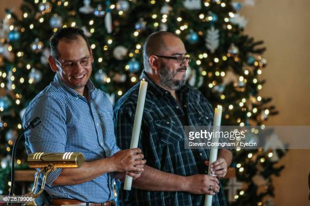 men holding lit candles by christmas tree - steven cottingham stock-fotos und bilder
