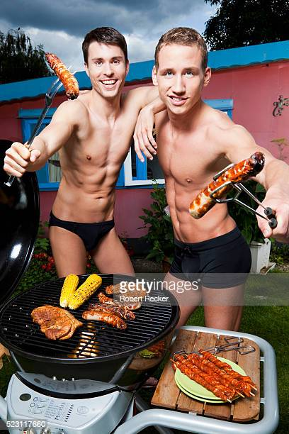 Men holding sausages while barbecuing