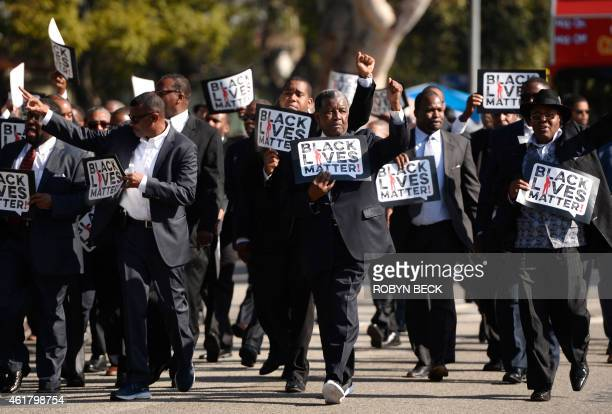 "Men holding signs reading ""Black Lives Matter"" march in the 30th annual Kingdom Day Parade in honor of Dr. Martin Luther King Jr., January 19, 2015..."