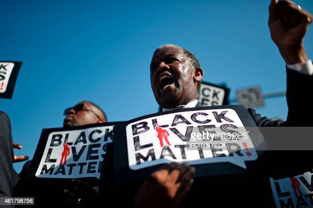 Men holding signs reading 'Black Lives Matter' march in the 30th annual Kingdom Day Parade in honor of Dr Martin Luther King Jr January 19 2015 in...