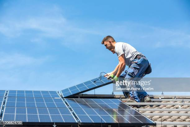 men holding solar panel while standing on roof against sky - solar energy stock pictures, royalty-free photos & images